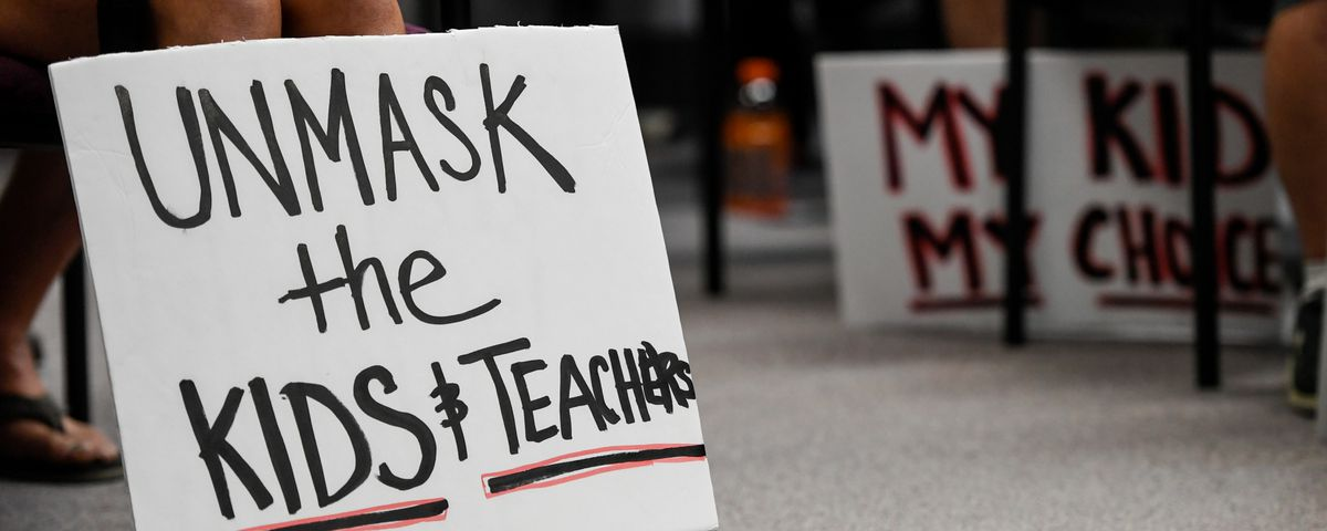 """A person holds a sign that reads """"unmask the kids & teachers"""" during a protest at a board of education meeting."""
