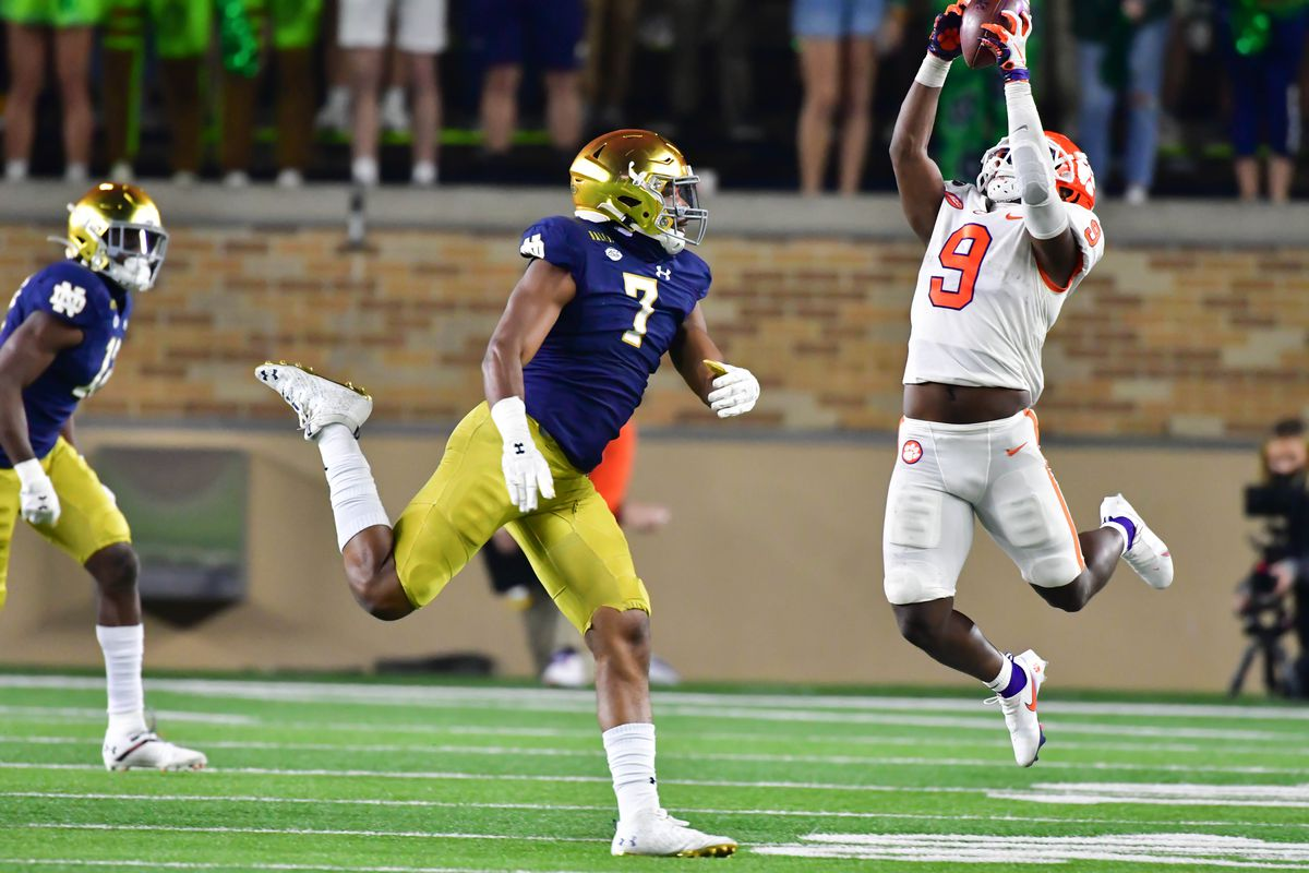 Running back Travis Etienne of the Clemson Tigers catches a pass as defensive lineman Isaiah Foskey of the Notre Dame Fighting Irish defends in the third quarter at Notre Dame Stadium on November 7, 2020 in South Bend, Indiana.
