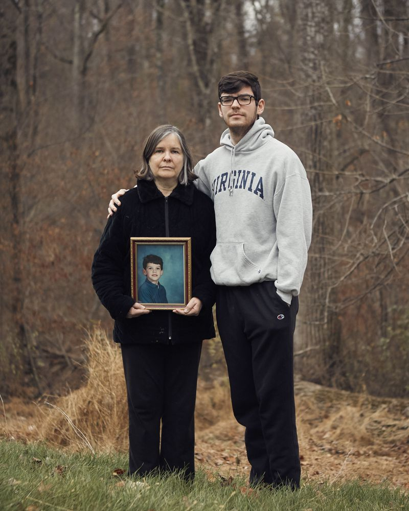 O'Reilly, holding a picture of her son Ed Fahy, with her other son William Fahy in their backyard.