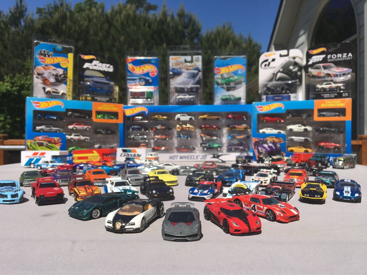 Photo of many Hot Wheels car displayed in a fan formation, with still-boxed and presumably highly valuable cars in the background.