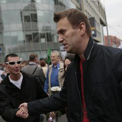Opposition leader Alexei Navalny, front, shakes hands with a supporter during a protest demonstration in Moscow, Saturday, Sept. 15, 2012. Thousands of protesters marched across downtown Moscow on Saturday in the first major rally in three months against President Vladimir Putin, while defying the Kremlin's ongoing efforts to crackdown on opposition.