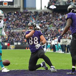 Baltimore Ravens tight end Dennis Pitta, center, flips the ball after scoring a touchdown in front of Miami Dolphins cornerback Bobby McCain, left, and Ravens wide receiver Kamar Aiken in the first half of an NFL football game, Sunday, Dec. 4, 2016, in Baltimore. (AP Photo/Gail Burton)