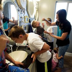 Gabe Hyde, left, Dax, Will, and Davis brush their teeth before bed with their mother Camilla and 1-year-old Hazel in Syracuse on Thursday, Aug. 1, 2013.