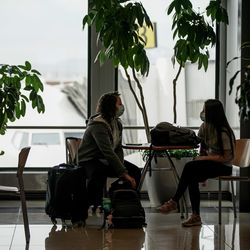 Kaitlin Perrenoud and Karson Adamson, both on their way home in Arkansas, sit together at Salt Lake City International Airport on Thursday, April 30, 2020. Like airports all over the world, Salt Lake's airport has seen air traffic plummet due to the COVID-19 pandemic.