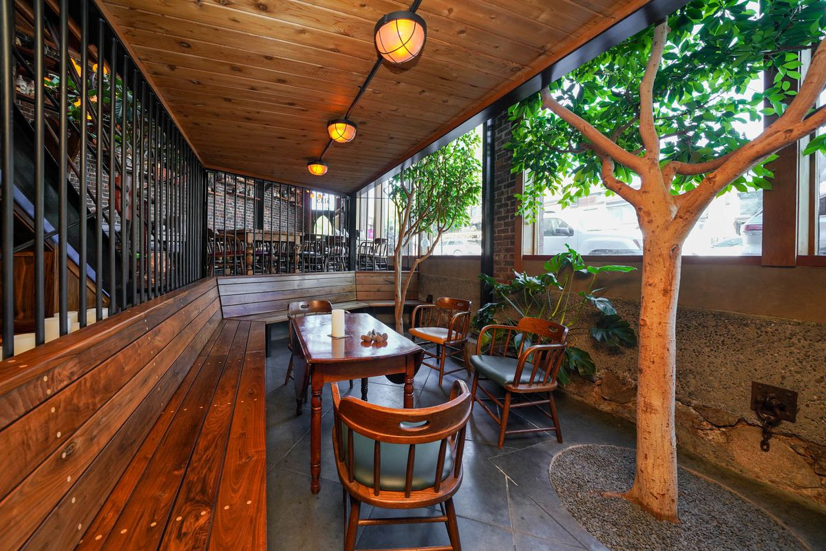 The dining area inside the Splintered Wand with wood chairs and tables, as well as live trees sprouting to the right.