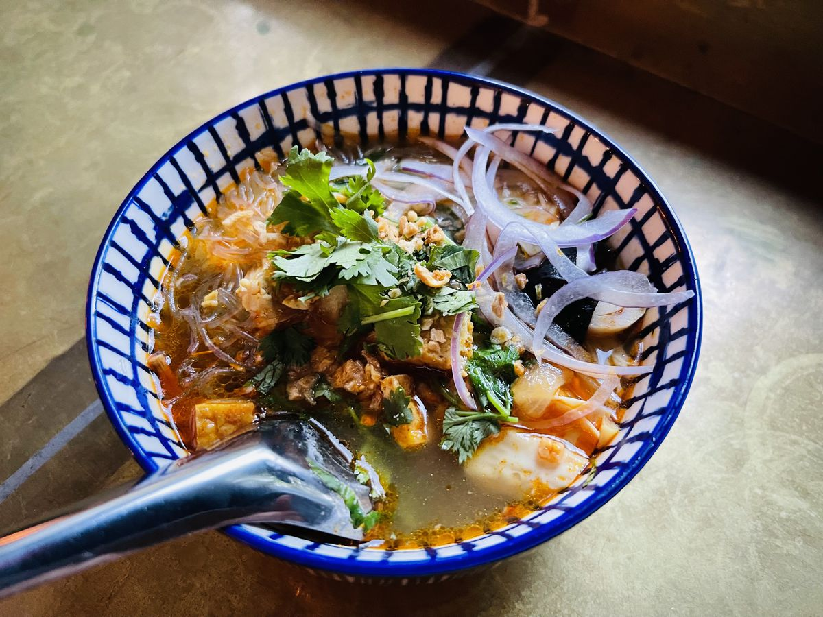 A bowl of soup comes topped with cilantro, thinly sliced onion, and tofu at Burma Joy in Portland, Oregon