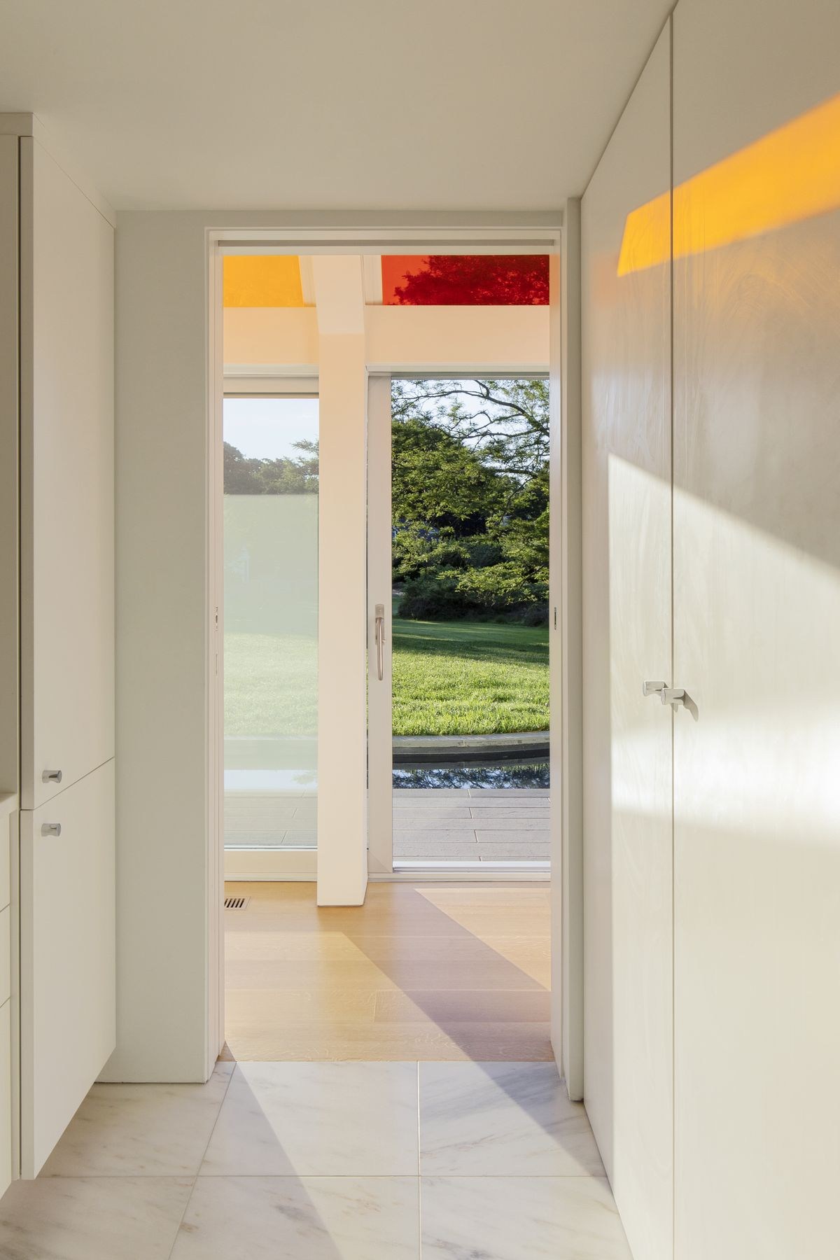 Entryway with white walls and an orange strip of reflection.