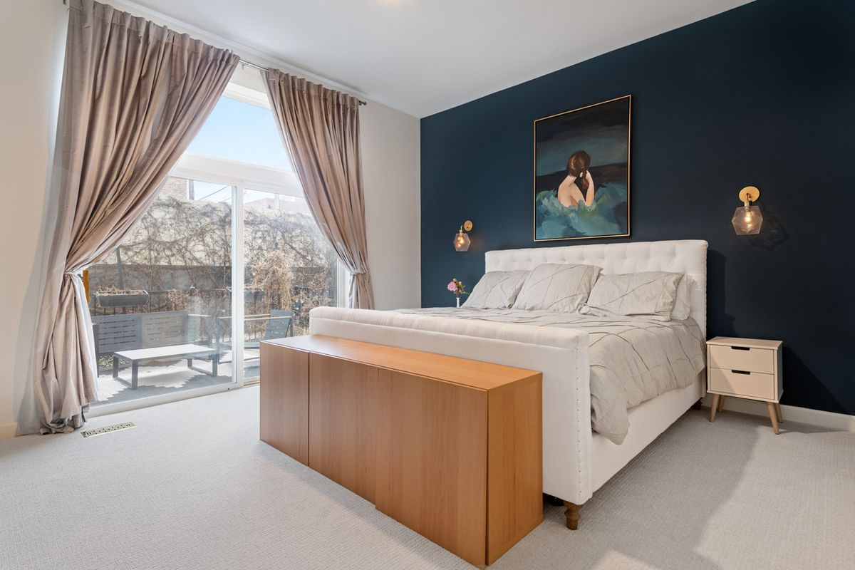 A white bed centered on a dark blue accent wall. There's a wood footlocker at the foot of the bed and a sliding glass door leading to an outdoor space.