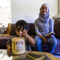 Zain Bilal, 3, eats spoonfuls of sugar while his sister Nour, 15, watches and laughs at their home in Millcreek on Tuesday, Sept. 8, 2015.