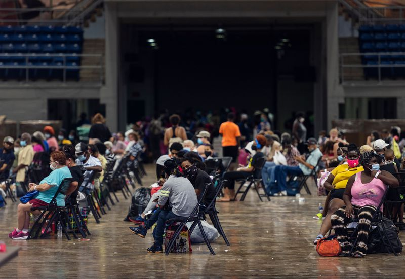 A hall with clusters of black chairs about 6 feet apart, is full of people — largely Black people — in their summer wear, masked and sitting with their bags.