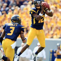West Virginia quarterback Geno Smith (12) jumps for a high snap before handing off to Stedman Bailey (3) during their NCAA college football game against Baylor in Morgantown, W.Va., Saturday, Sept. 29, 2012.