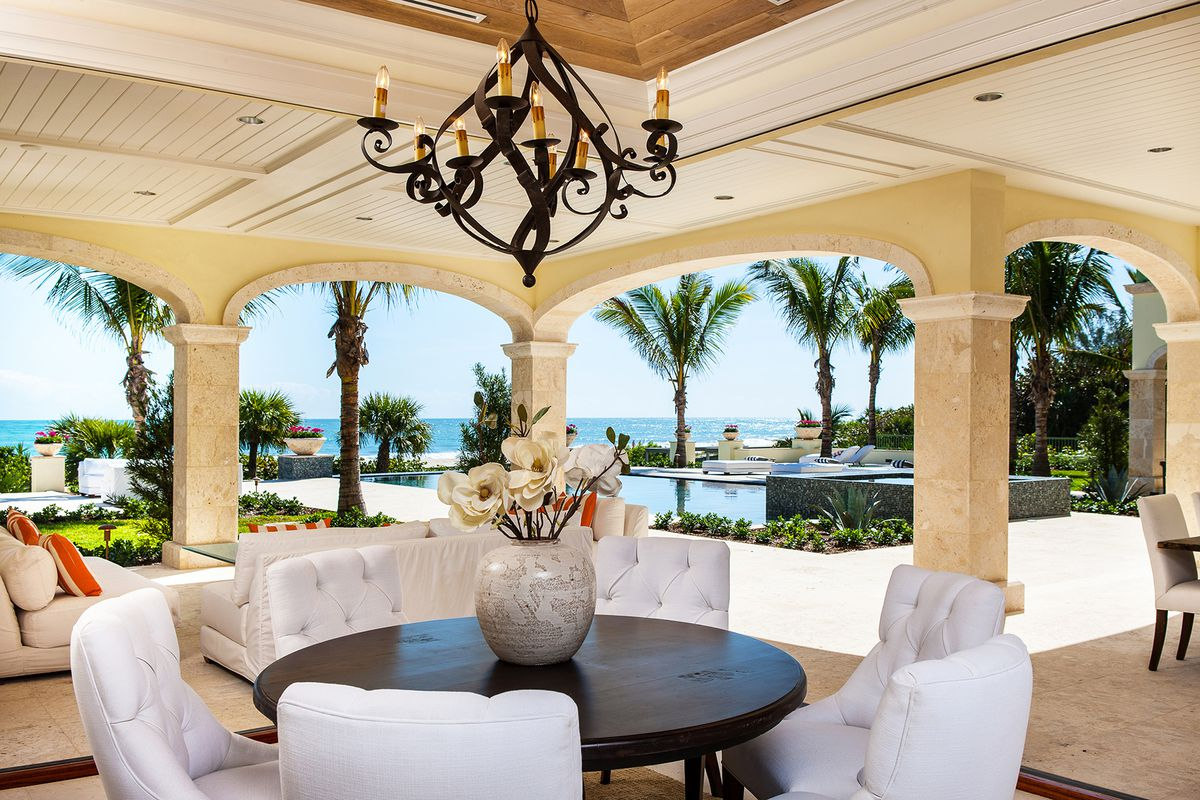 An oceanfront home in Vero Beach is heading to auction, showing the view of the pool amid a beach landscape