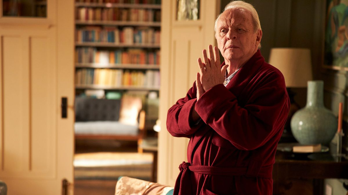 Anthony Hopkins in a bathroom, clasps his hands together, standing in an apartment.