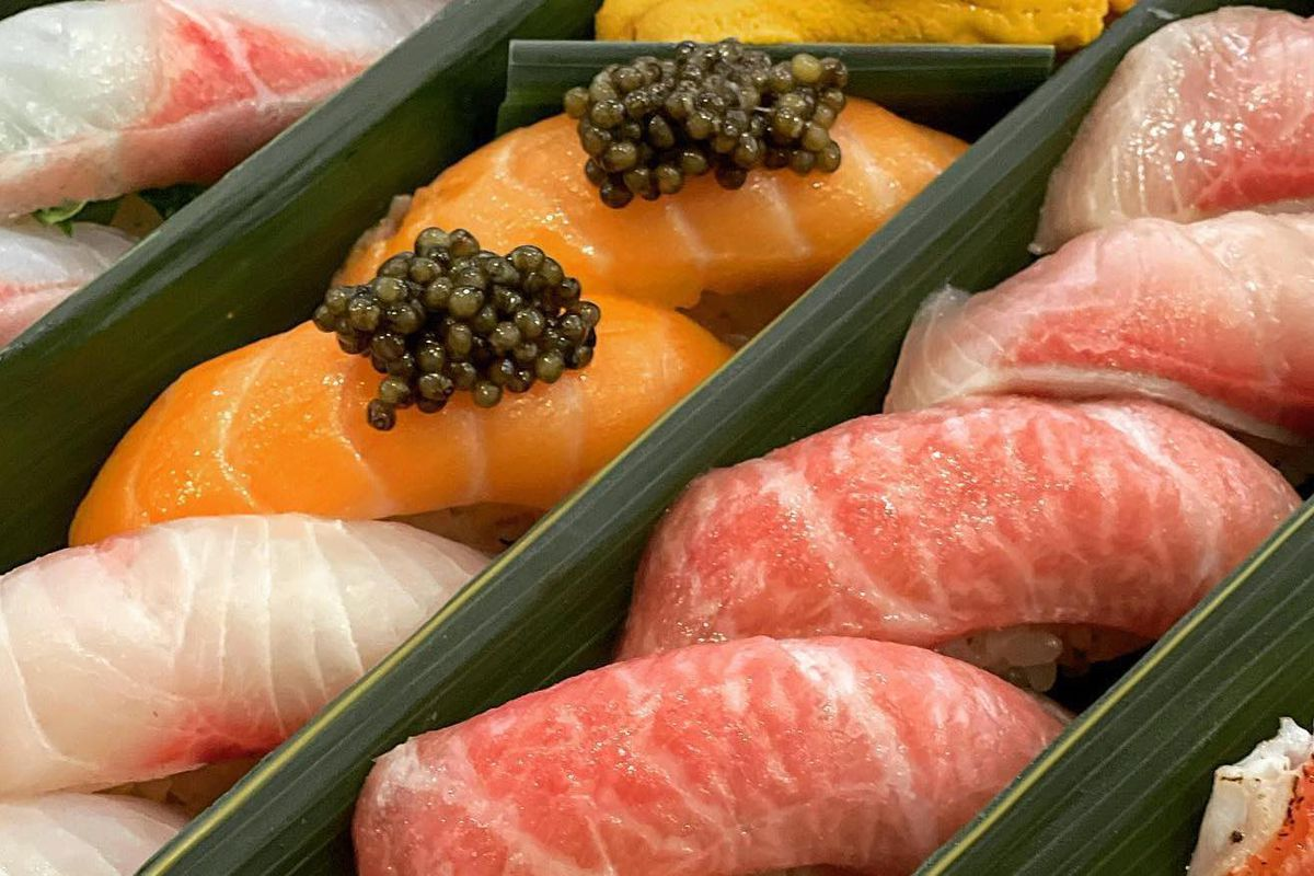A close up shot of sushi inside of a takeout box, with caviar on top.
