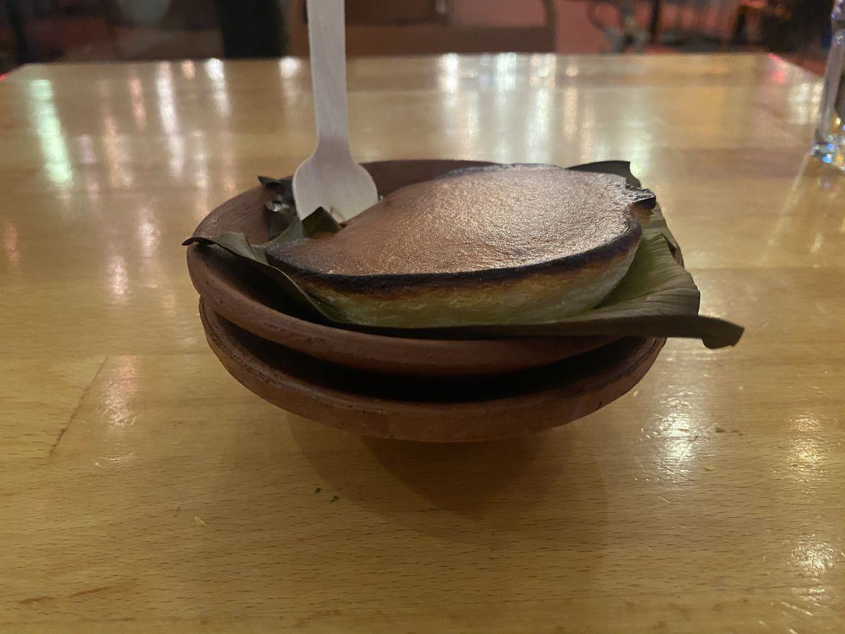 A baked cheese dessert with a burnt top sits in a small clay bowl lined with a banana leaf.