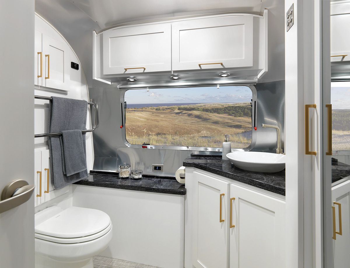 A bathroom inside the travel trailer features white cabinets, black countertops, and brass hardware.