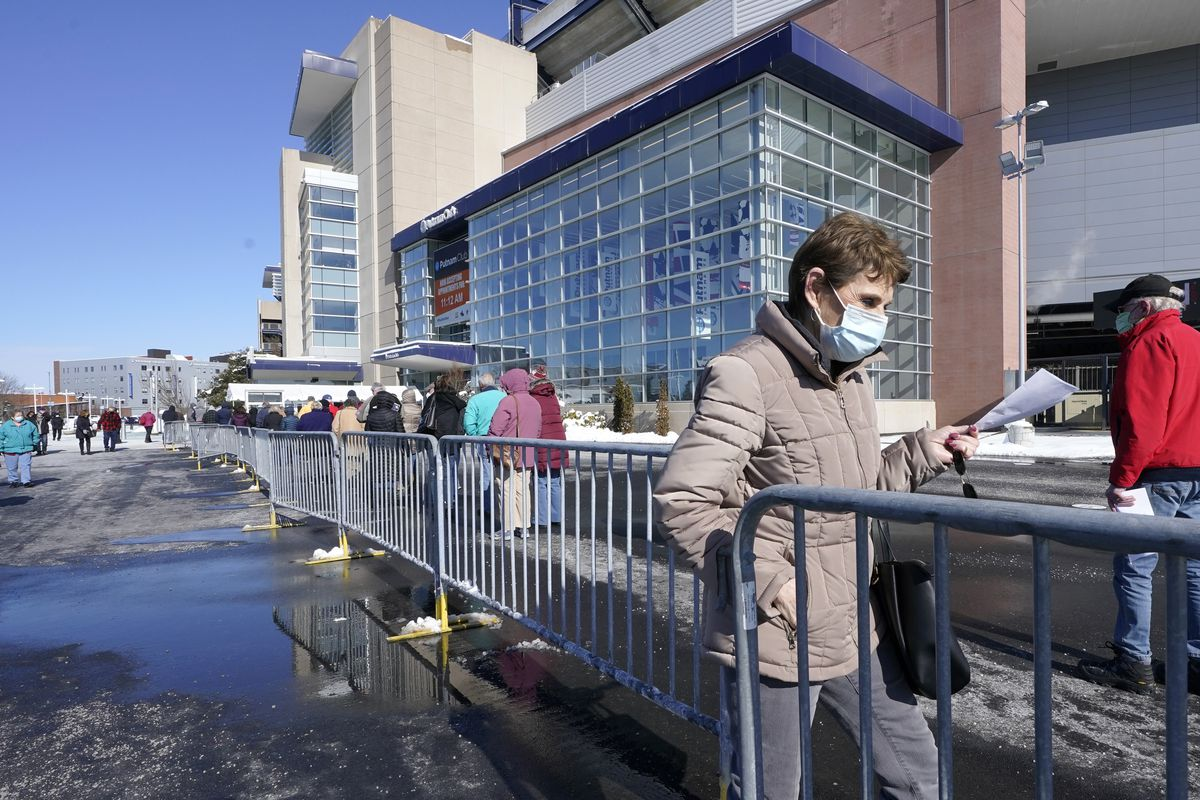 People enter a socially distanced line to get their COVID-19 vaccinations at Gillette Stadium, Monday, Feb. 8, 2021, in Foxborough, Mass.