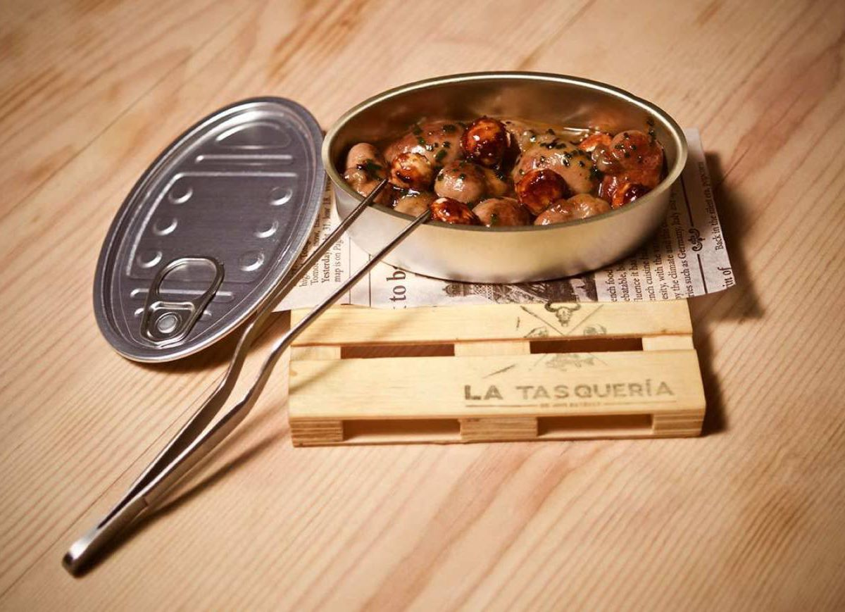 A tin holding rabbit kidney lies open next to the tin's top and a serving skewer. The tin sits on a mini wooden palette branded with La Tasqueria's name.