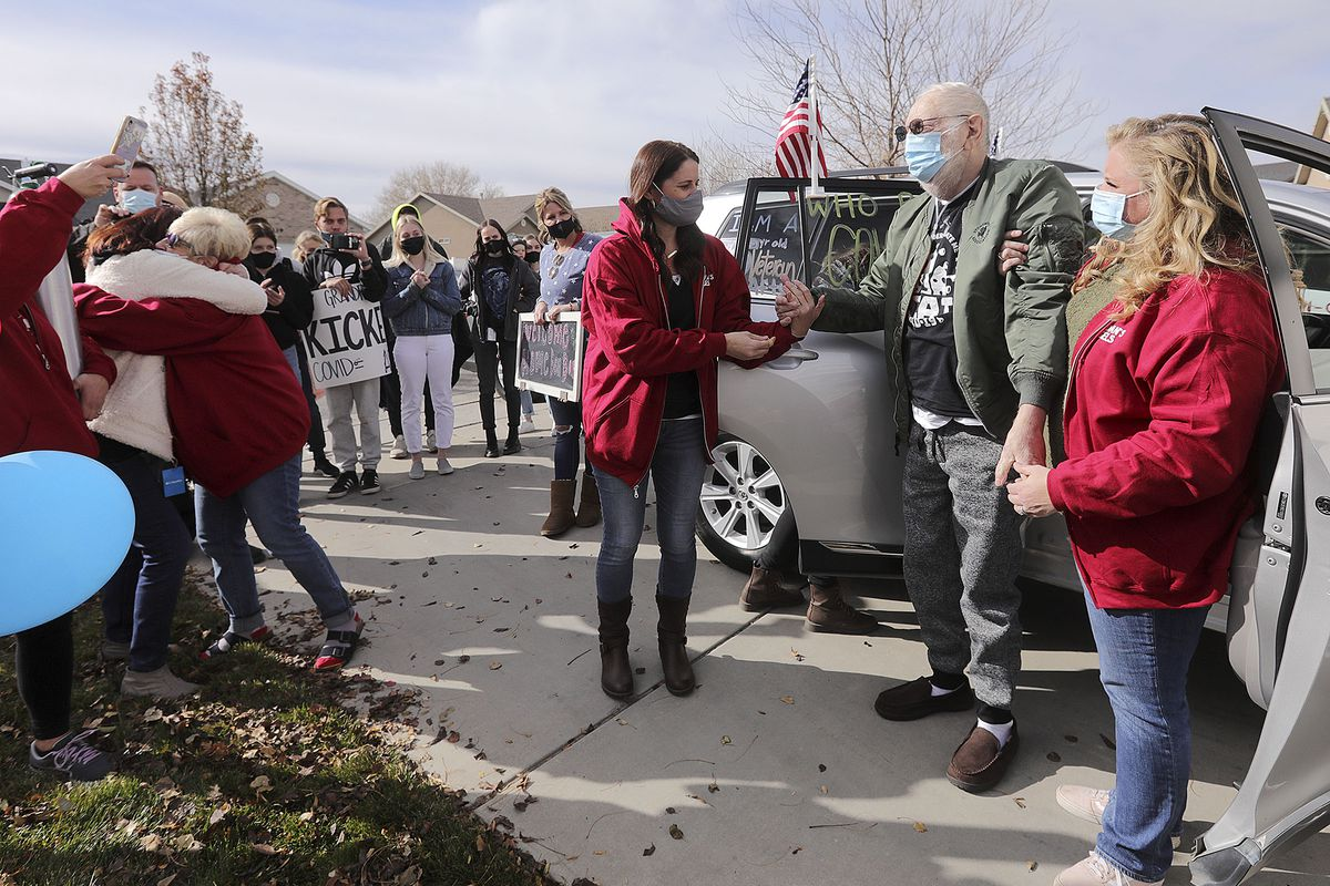 Vietnam veteran Warren Craig Eby, right center, is assisted by daughters Alissa Allen, left, and Lauren Cooper, right, during a welcome home celebration in Saratoga Springs on Friday, Nov. 13, 2020. Eby was hospitalized for seven weeks with COVID-19. At far left, Eby's wife, Sandra, hugs their niece Cindy Lampropoulos.