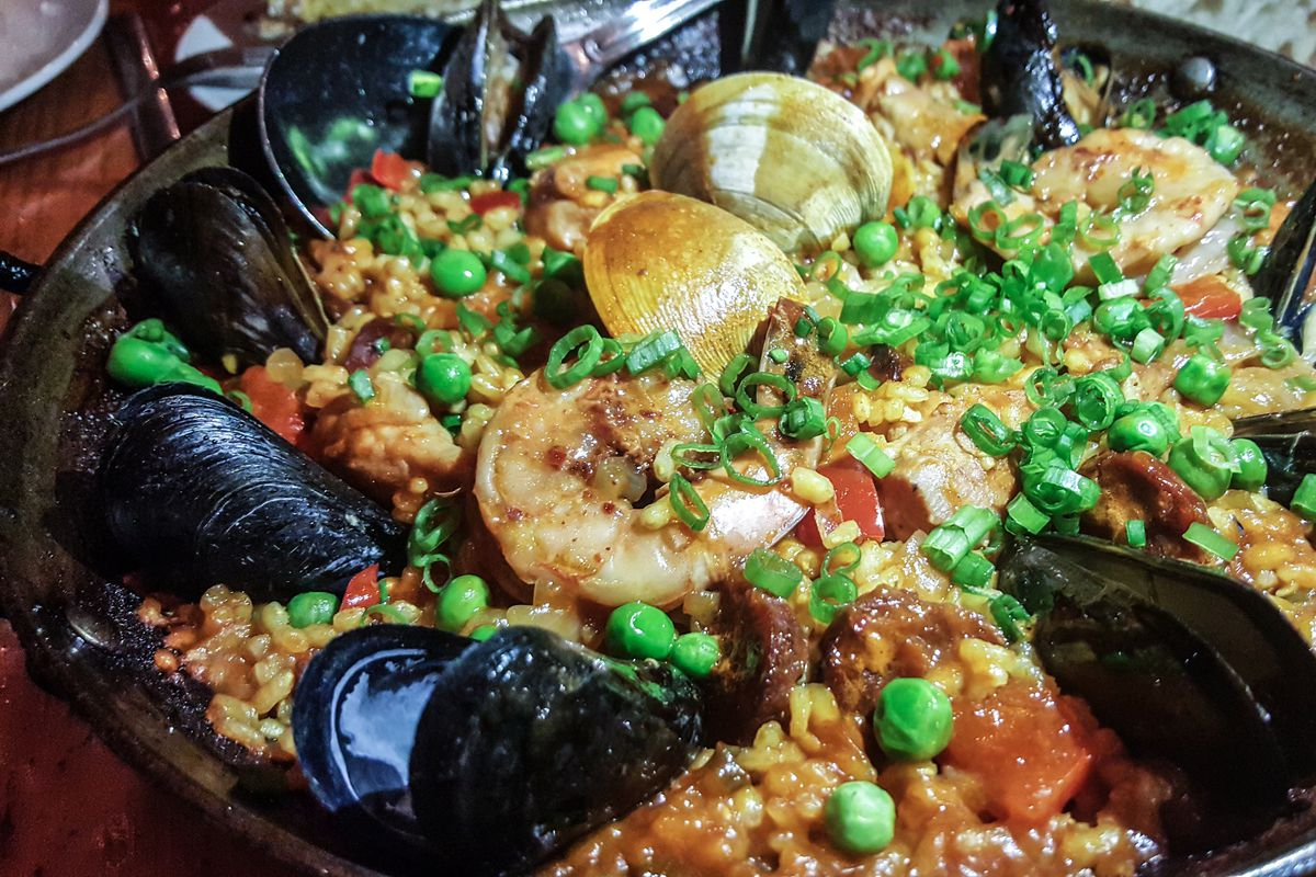 Mussels, shrimp, and clams sit atop a skillet of rice and vegetables