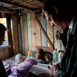 Elder Tanner McKee, right, reads from the Book of Mormon as he and his companion, Elder Pedro Cabral, left, both missionaries for The Church of Jesus Christ of Latter-day Saints, visit with a bedridden woman in her home in Paranaguá, Brazil, on Sunday, June 2, 2019.