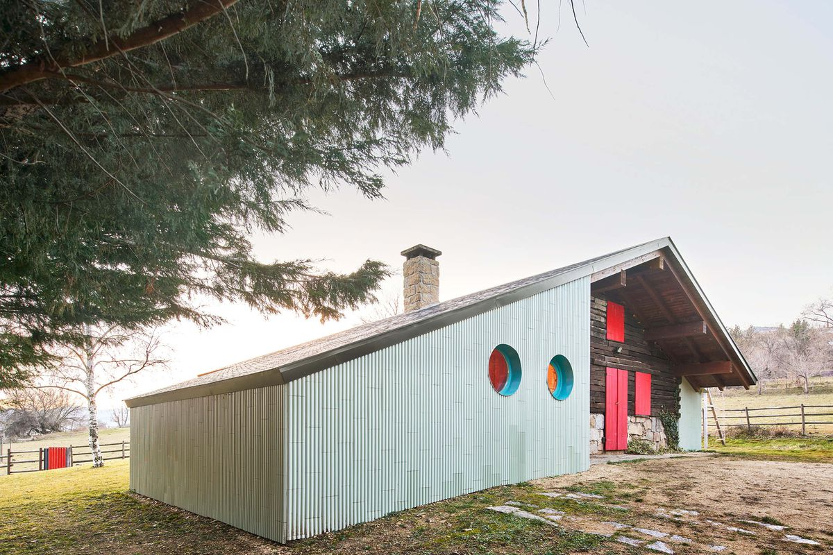 Colorful house in the countryside features sloped roof with red accents and two circular windows.