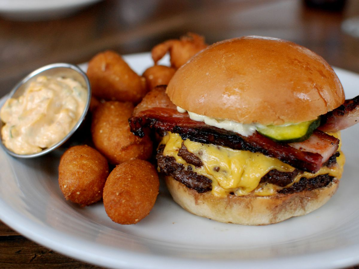 A cheeseburger with bacon and a side of hush puppies