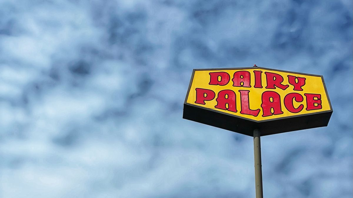 """A yellow sign set against blue skies. In red, the sign reads """"Dairy Palace"""""""