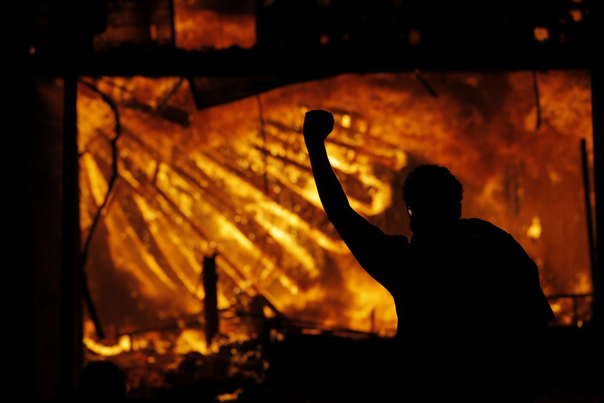 A protester gestures in front of the burning 3rd Precinct building of the Minneapolis Police Department on Thursday, May 28, 2020, in Minneapolis. Protests over the death of George Floyd, a black man who died in police custody Monday, broke out in Minneapolis for a third straight night.