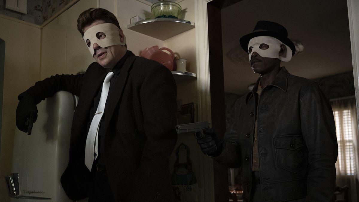 Benecio del Toro and Don Cheadle in dark suits and terrible white felt masks in No Sudden Move