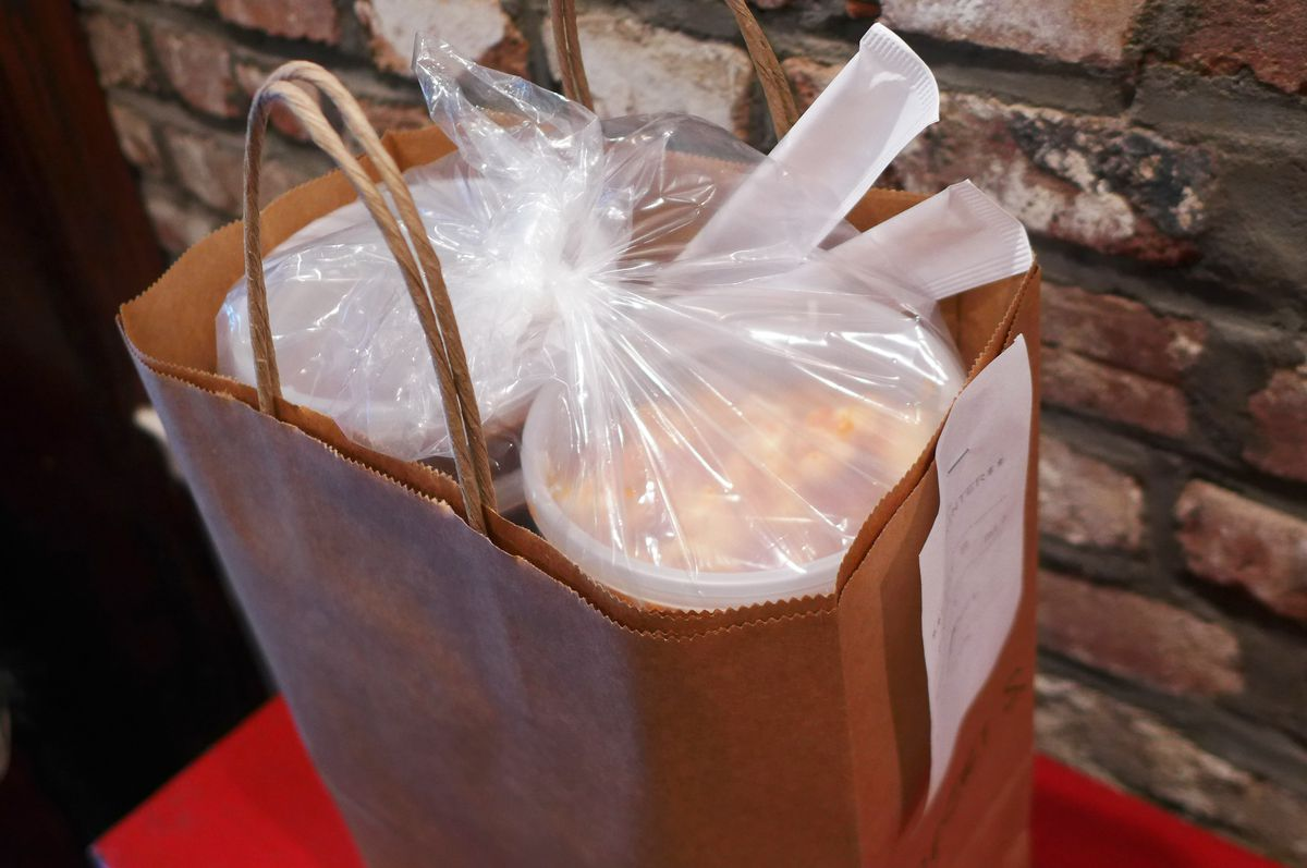 A brown paper bag with handles and plastic containers visible on top.