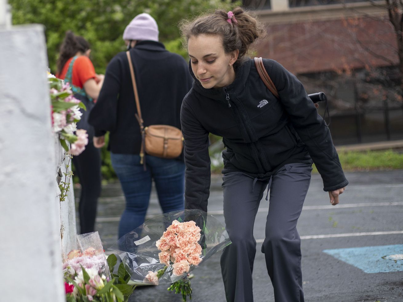 A woman places flowers near a makeshift memorial outside of the Gold Spa in Atlanta, Wednesday, March 17, 2021.