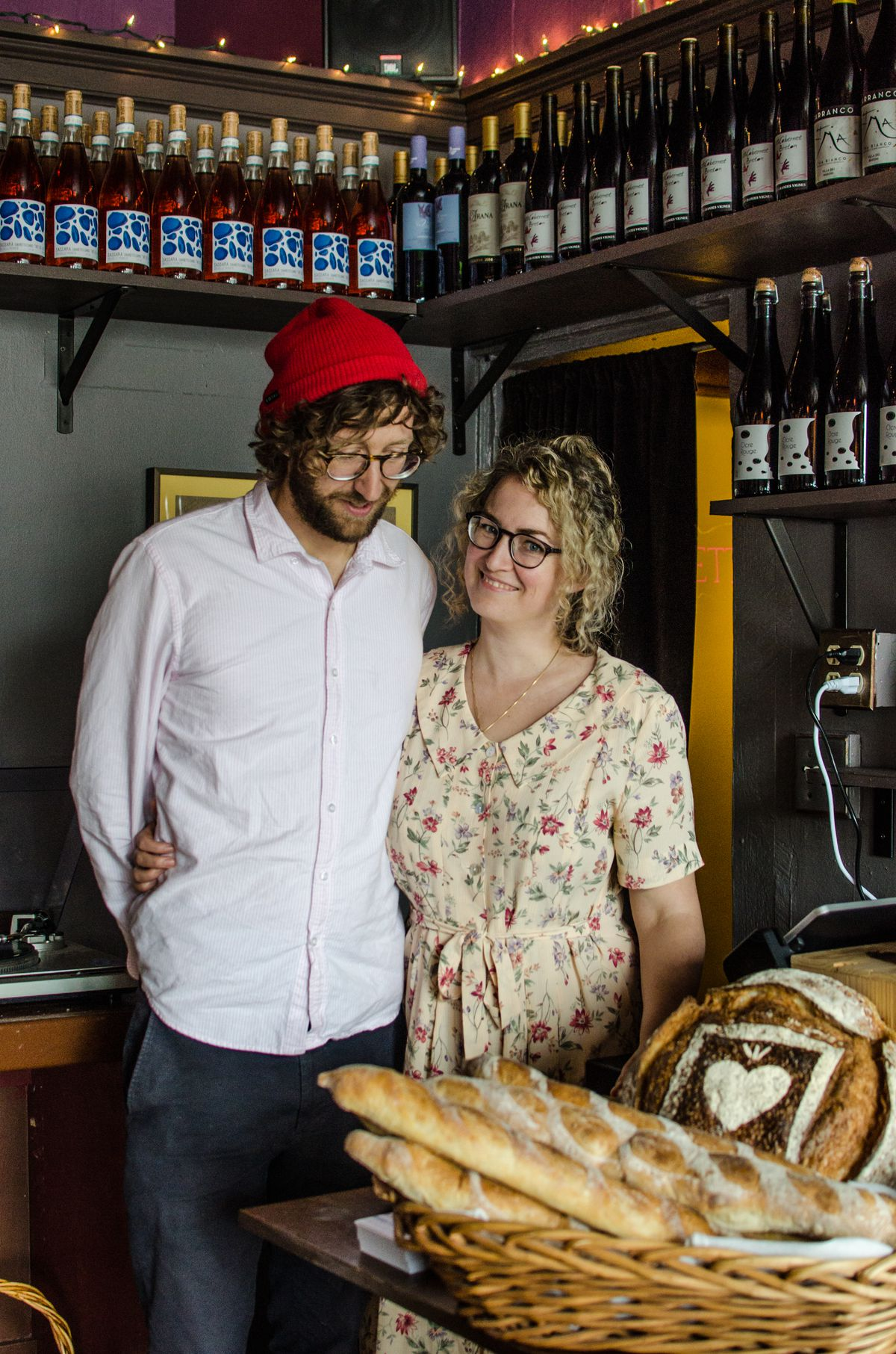 A man and a woman, each with glasses and curly hair, stand in a corner of a wine bar. A basket of bread is in front of them. The woman, in a flowered dress, looks at the camera, while the man, in a button-down pale pink shirt, jeans, and red beanie, looks down.