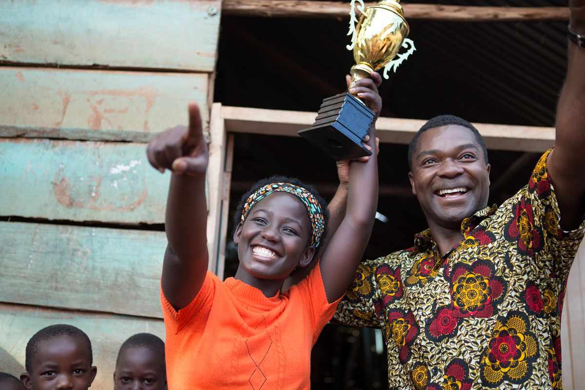 "Madina Nalwanga and David Oyelowo holding a trophy in ""Queen of Katwe"""