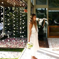 """""""Although we hadn't planned anything, we did end up getting flower garlands. I wore a <b>Maison Martin Margiela</b> dress that I found at <b>Maxfield</b> [8825 Melrose Ave] literally 30 minutes before the wedding! I was barefoot."""" — Ambre Dehan, <a"""