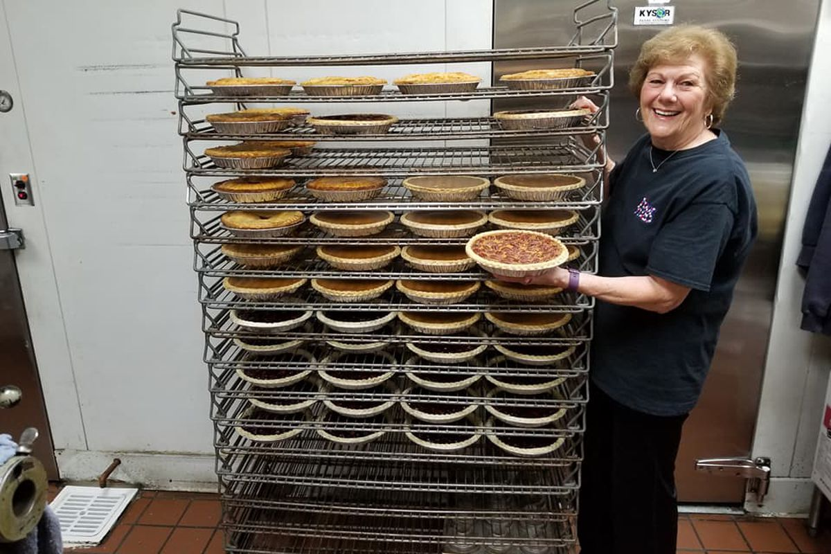 A rack of pies as one older woman holds a single pie up for the camera.
