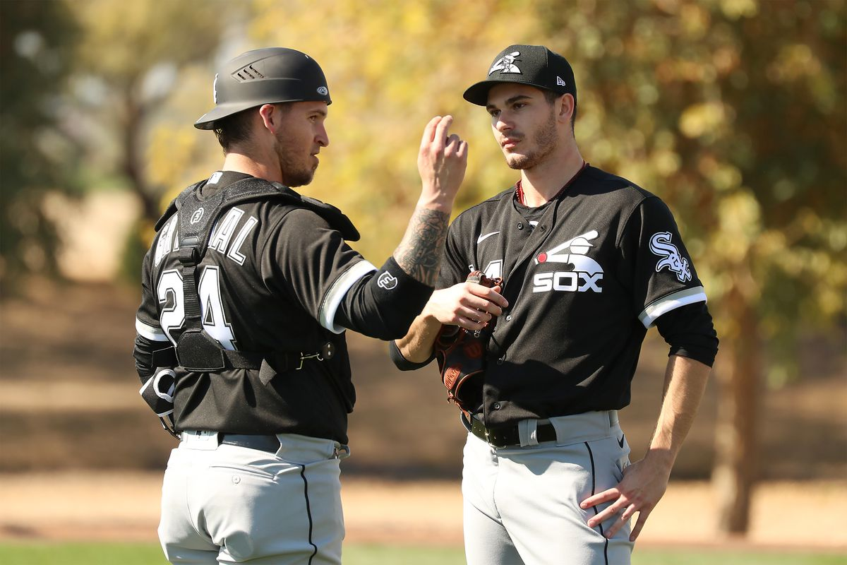 Catcher Yasmani Grandal confers with Dylan Cease after Cease's sideline session at Camelback Ranch.