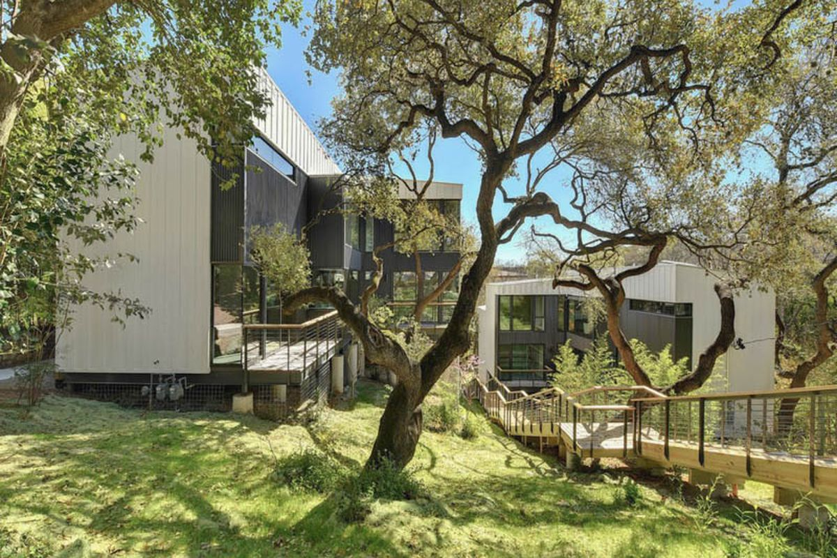 A green, sloping lot with willowy trees and a contemporary white-stucco-and-metal building