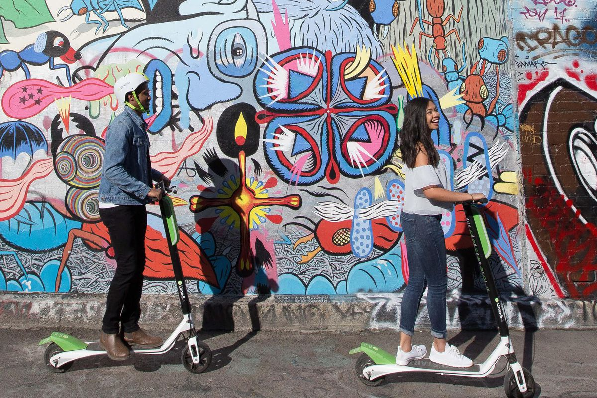 A picture of two people using lime scooters past a heavily decorated wall.