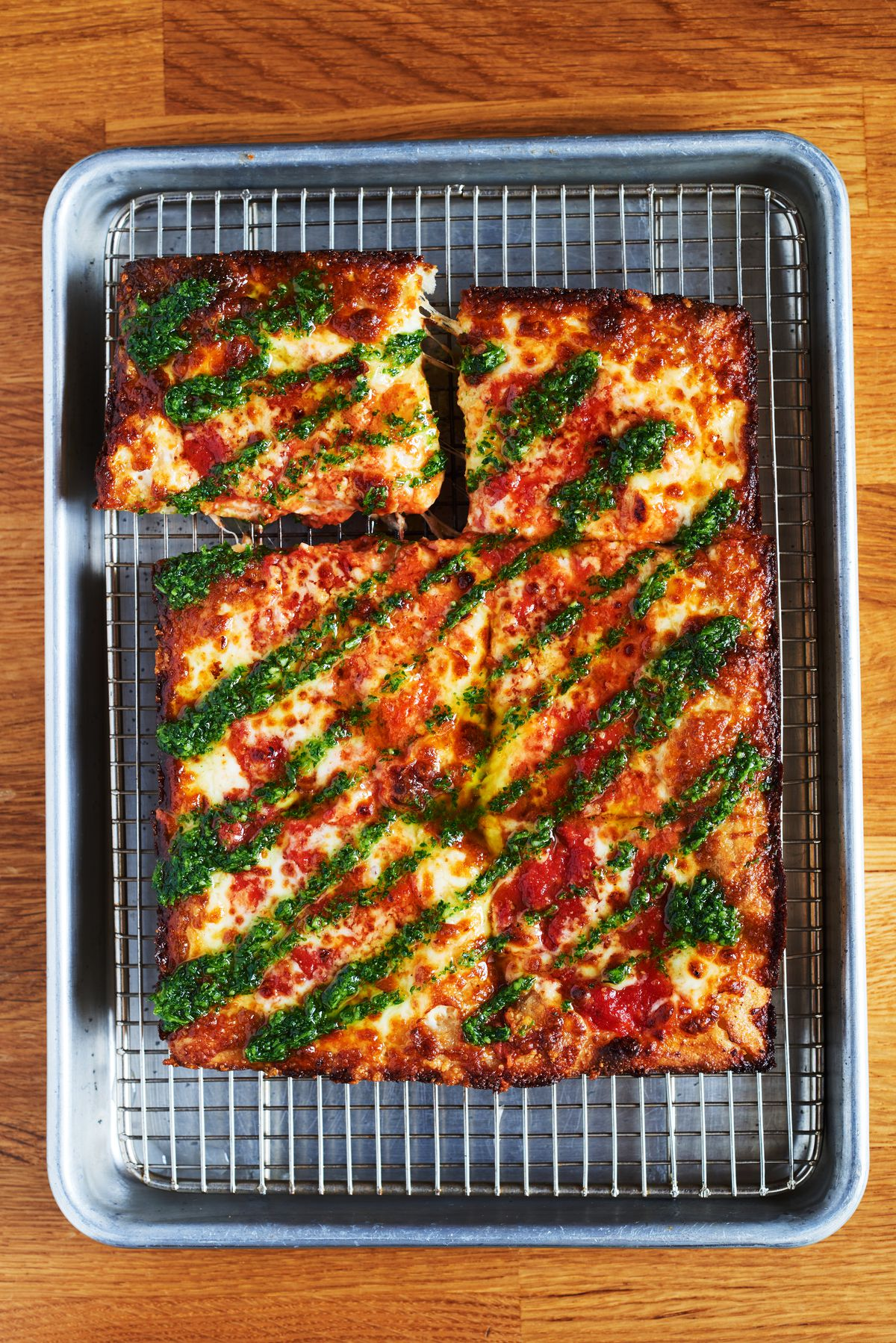 Six, thick square slices of the MVP pizza topped with red sauce, vodka sauce, drizzled with bright green pesto
