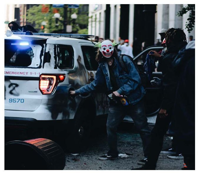 A man alleged to be Timothy O'Donnell reaches toward the gas tank of a Chicago police vehicle in Chicago.