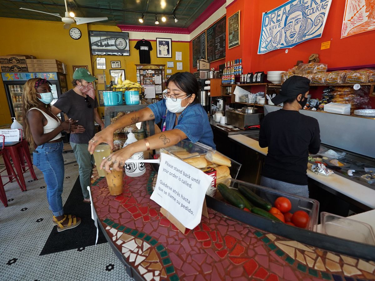 Customers wait in line in a coffeeshop as a woman in a facemask puts two plastic cups on the countertop.