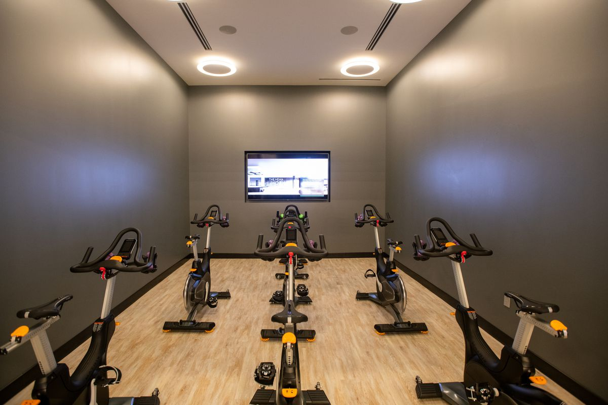 A cycling room with six spin bikes facing a TV screen.