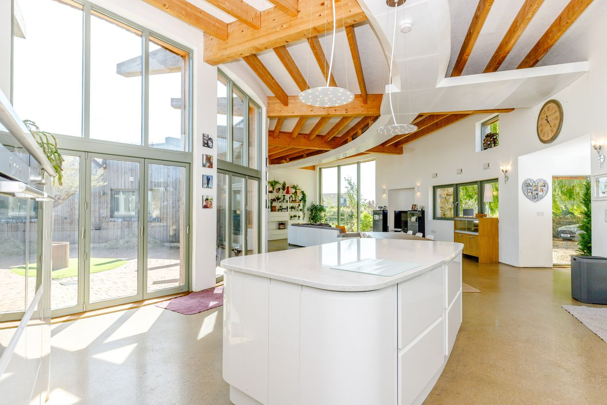 Kitchen surrounded by floor to ceiling windows, wooden beams in the ceilings, and a white island.