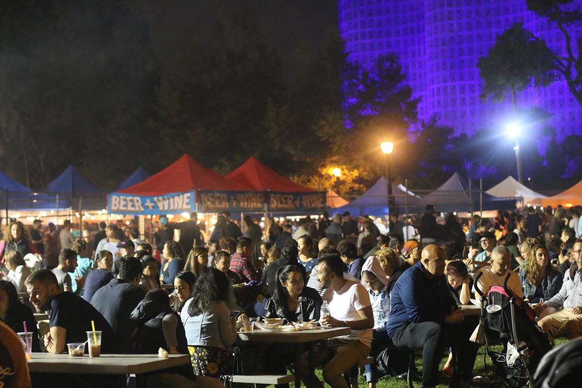 A large crowd of people sitting at tables during an outdoor food market at night