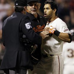 San Francisco Giants' Angel Pagan, right, is held back by manager Bruce Bochy, center, as he argues with home plate umpire Angel Hernandez after a strike out during the sixth inning of a baseball game against the Colorado Rockies on Tuesday, Sept. 18, 2012 in San Francisco.
