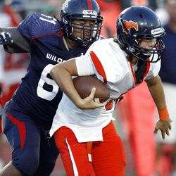 Woods Cross' #61 Deion Saumalu, left, chases down Mountain Crest's #5 Jamison Webb in the second quarter of play Friday, Aug. 31, 2012.
