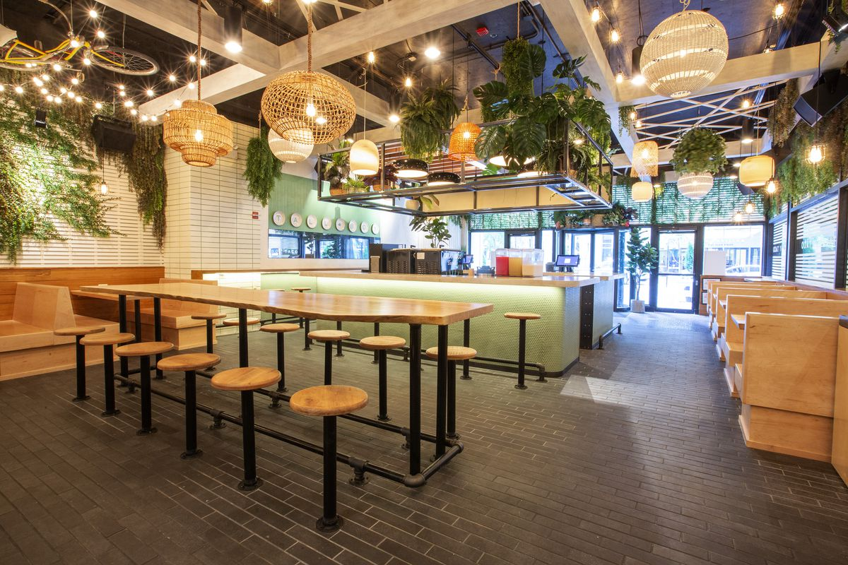 A restaurant interior with light wood tables, stools, and booths.