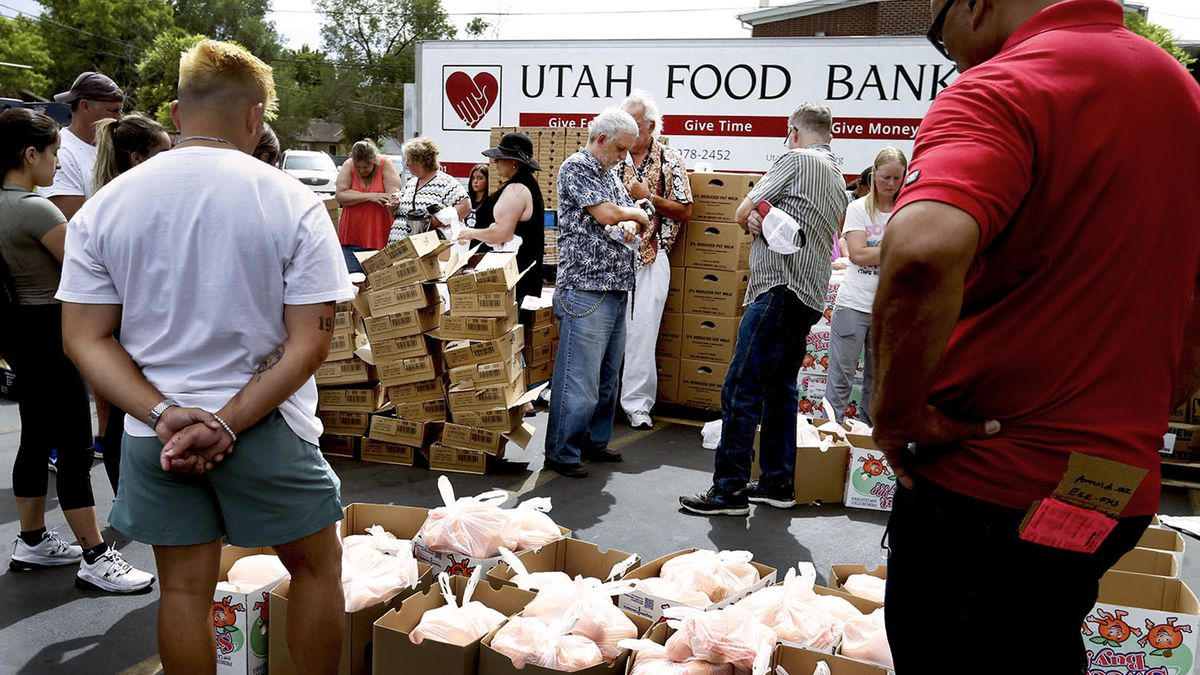 Volunteers pray before handing out food at the Utah Food Bank mobile pantry at The Church of Jesus Christ of Latter-day Saints Cannon Stake Center. Food banks have played a key role, along with government aid, in holding food insecurity pretty stable in the pandemic.