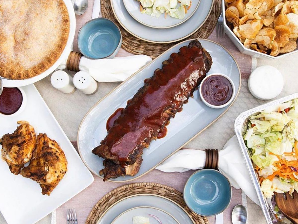 A table filled with gold-rimmed dishes, including a plate of sauce-covered ribs in the center, chips, salad, chicken, and pie